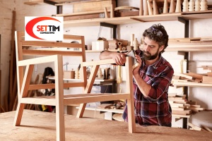 Serious furniture designer carefully sanding a chair frame that he is busy manufacturing in his woodwork studio, with shelves of wooden items behind him